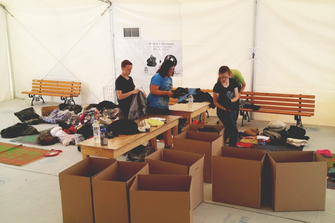 Sorting boxes of clothing donations for refugees.