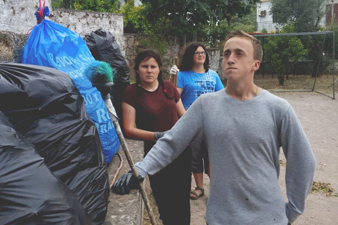 Cleaning up around a refugee area in Greece.